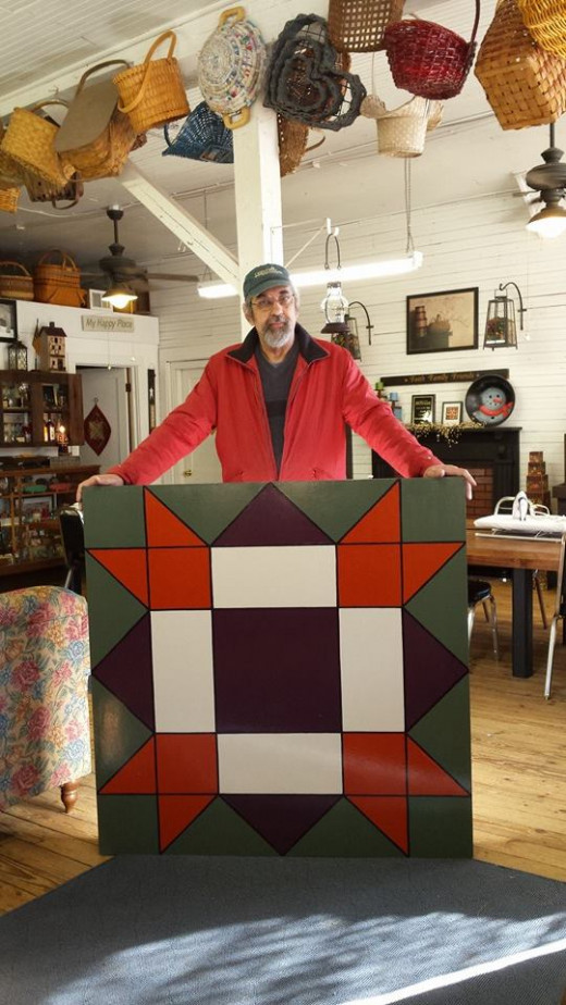 Volunteer Stephen Filarsky, who with his wife Theresa came up with the quilt trail idea, paints the design on one of the quilt blocks