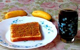 Two bananas, coconut custard jam on bread, and ginger tea.