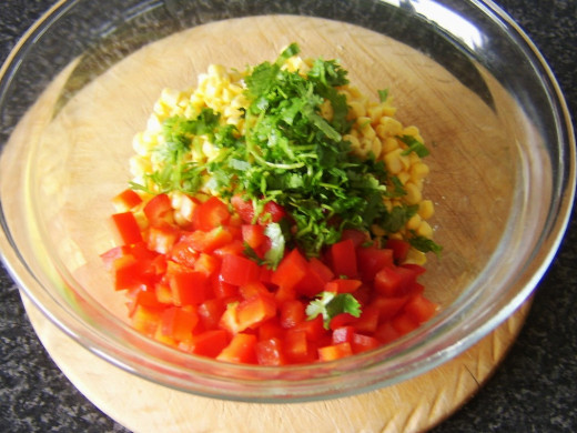 Corn, bell pepper and herb is added to the peas