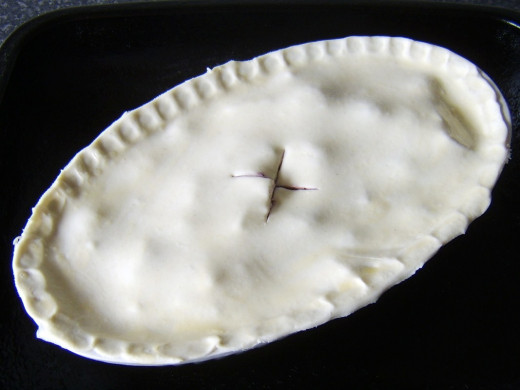 Pie is glazed, a steam vent is cut and it is ready for the oven