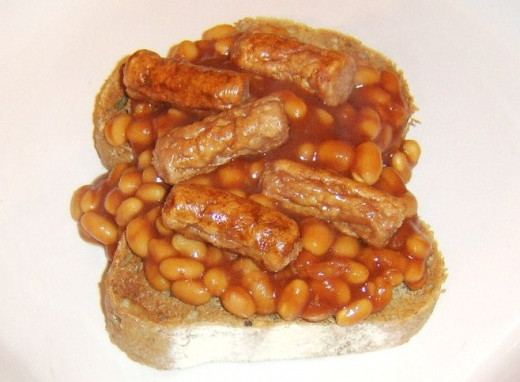 Mini sausages are laid on beans on toast