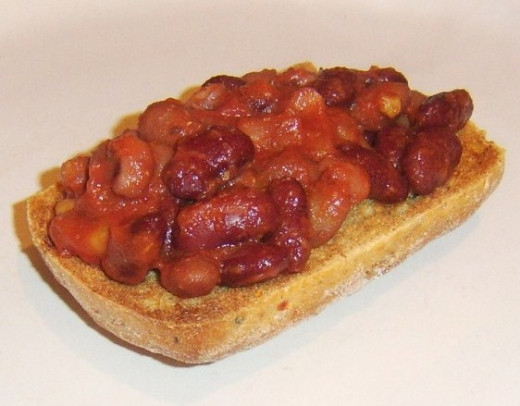 Five bean salad in tomato sauce is spread on ciabatta toast
