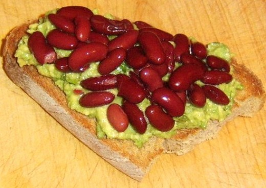 Red kidney beans are spread on guacamole on toast