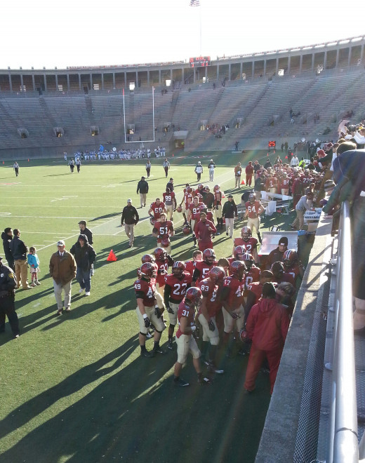 At halftime of the Columbia game, the Harvard players in uniform, along with the Columbia marching band in the distance, vastly outnumbered spectators in the stands.