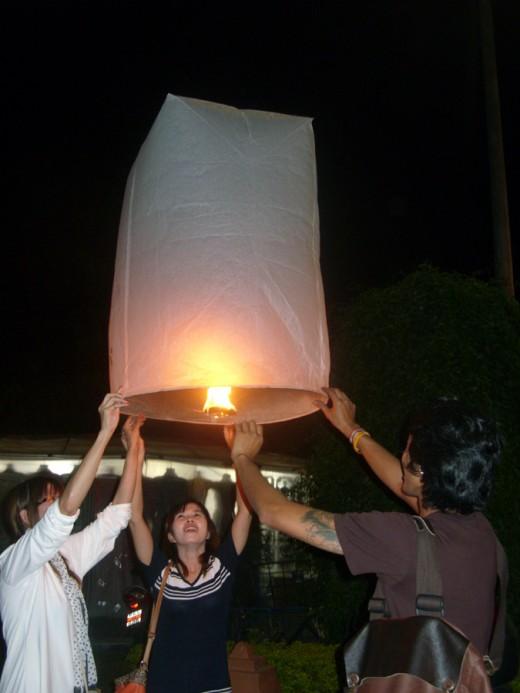 Launching a sky lantern (kom loi)