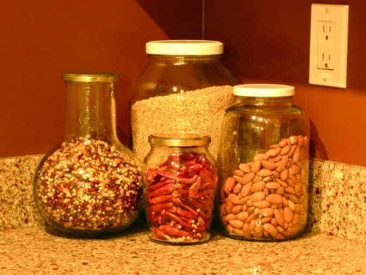 Kitchen counter: used grocery jars filled with brown rice, popcorn, almonds & dried hot peppers.