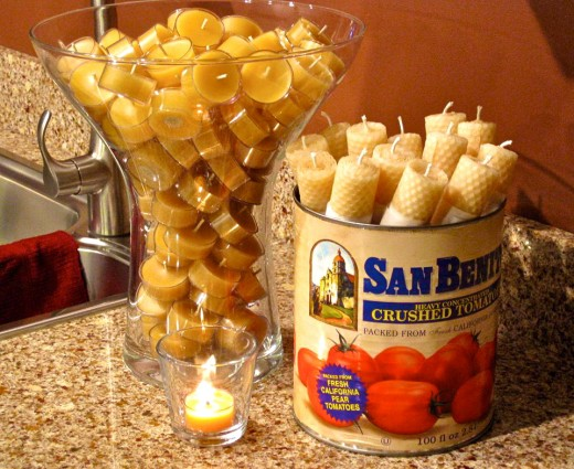 A uniquely shaped vase & old tomato can containing home-made beeswax candles.