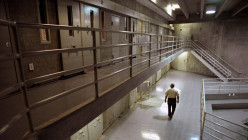 A corrections officer patrols the cell blocks in the California Dept. of Corrections.