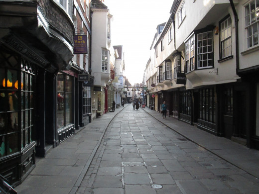 Stonegate seen from the junction with High and Low Petergate. 'Ye Old Starre Inn' is accessed through a passageway on the right below a banner that spans the street that bears its name