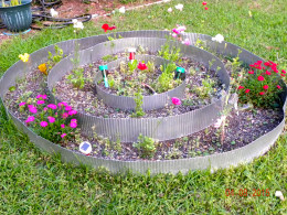 This planter has flowers.  Also, potatoes, and lettuce are planted.