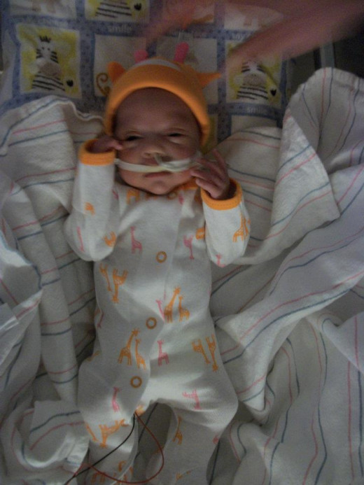 The first set of preemie clothes that fit her at 8 weeks