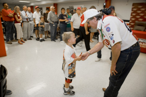 John Force, another legendary drag racer, greets a young fan.
