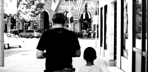 A back view of a father walking with his son