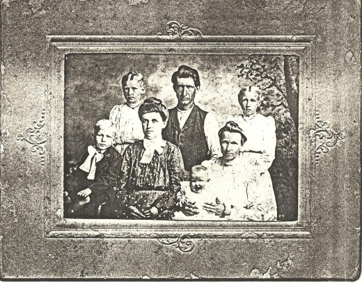 Melissa Tower married Henderson (Henry) Fiscus in 1896 in Arkansas. They later lived in Missouri and Oklahoma.  Henry in vest, Melissa holding grandchild.