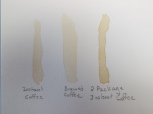 I tested the shades of the 'coffee paint' on  watercolor paper. The one in the middle is the 'brewed coffee' The left one is what the instant  coffee looked like before I added the second package, the right one is what it looks like now.