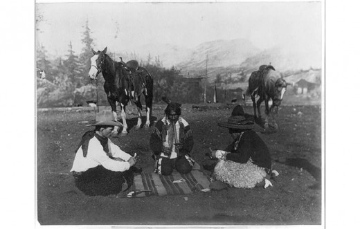 - Cowboy, Indian, and Mexican sitting on blanket in open field, playing cards; gun and knife are on blanket.
