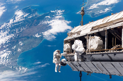 Astronauts on a space walk above the Earth.