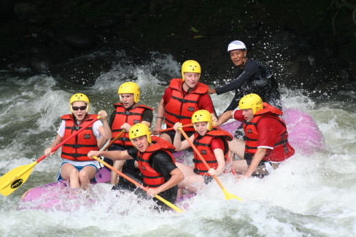 A family on a rubber raft experiencing white water rafting.