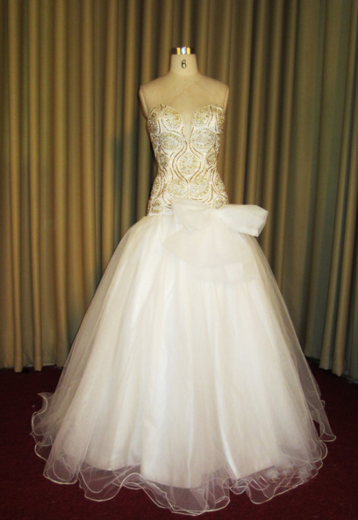 A pretty gold and white wedding dress in white and gold with a detachable bow.