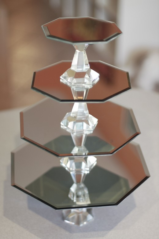 With just a few mirrors and some cande sticks from the dollar store you can make this delightful cake stand