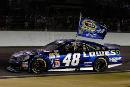 Jimmy Johnson drives around racetrack holding the flag of that racetrack.