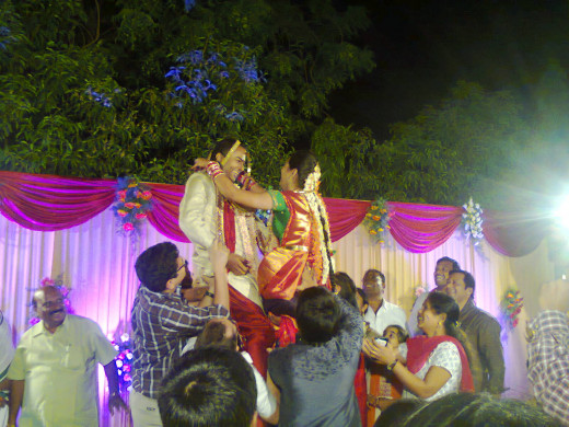 groom and bride lifted in air for garlanding each other