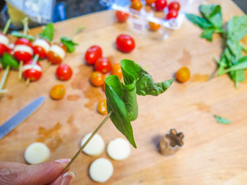 Once everything has been washed and cut, take a wooden skewer and slide a basil leaf.