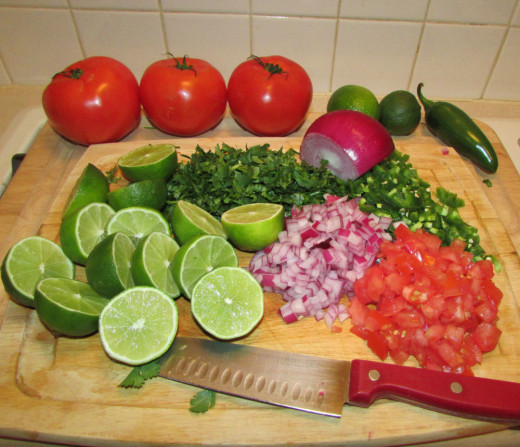 Chop some coriander, an onion, a tomato, a green chilly and lemons.