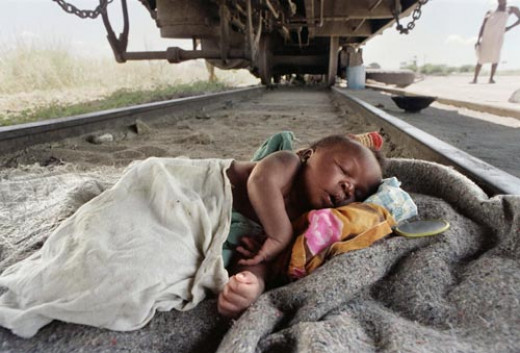 A baby sleeps under a railway wagon at a refugee camp
