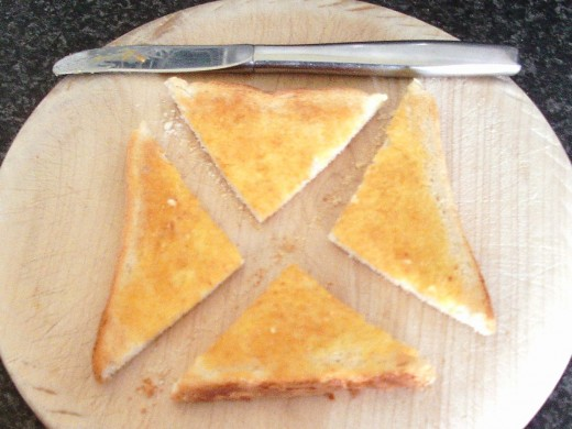Toast slice is quartered on chopping board