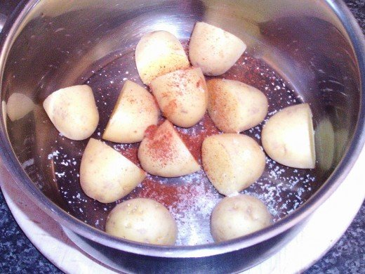 Salt and paprika are added to halved babay potatoes