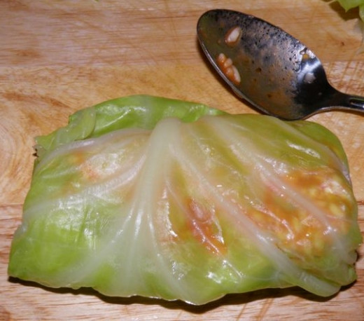The assembled stuffed cabbage rolls are either baked or gently simmered to cook, topped with a spicy sauce,