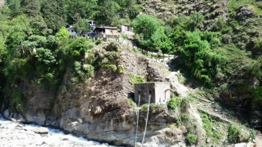 The cave-temple on the other side of Kalpa Ganga on the top of a hill. The old rope-bridge is visible