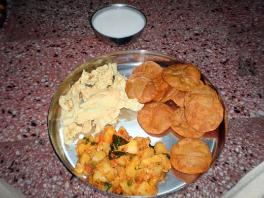 Masala Pooris served with aloo (potato) subzi, papads and dahi (curd)