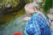 Myself as a child, collecting water from the well to fill a kettle for a pot of tea. Photo from the early 1990s.