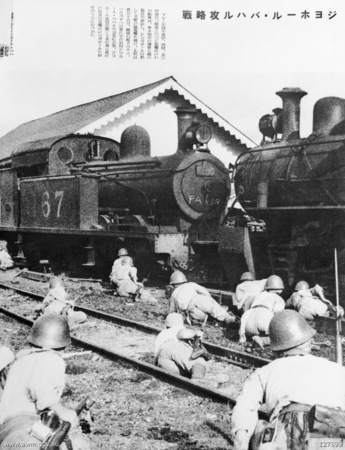 Japanese troops take cover behind a train.