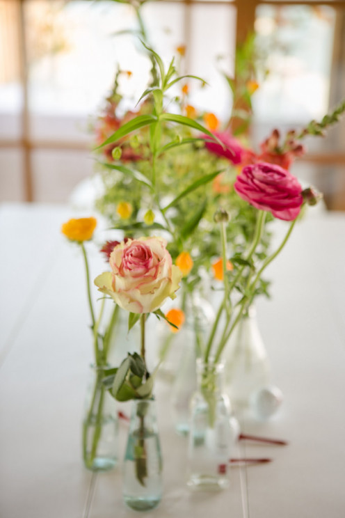 Skinny vases with single stems or small bouquets of flowers are perfect for summer apartment decorating.