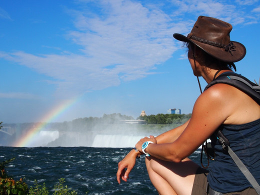 A woman enjoys the breathtaking view of Niagara Falls, adjoining Canada and the U.S.  Notice the rainbow that's in the background.