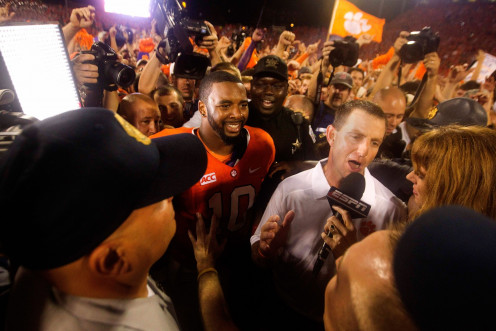 Dabo Swinney head coach of the Clemson Tigers tries to answer questions as Clemson fans rush the field.