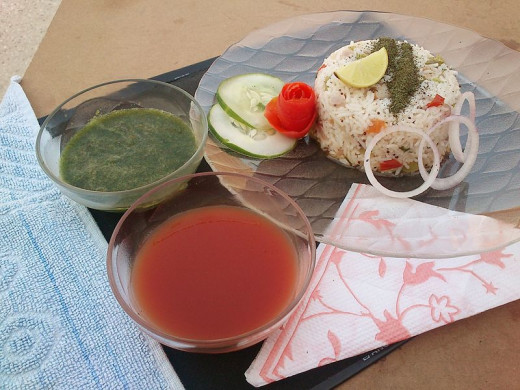 Vegetable Pulao served with pudina (mint leaves) and tomato chutneys, and salad