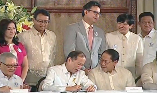 The Philippine President Benigno Simeon C. Aquino III signs the Philippine Enhanced Basic Education Reform or RA 10533 with Senator Angara and other government officials witnessing.