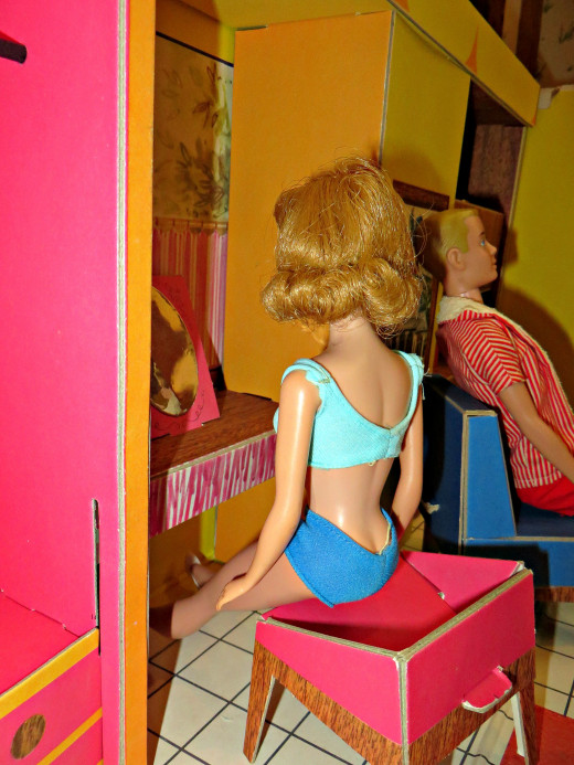 Midge, Barbie's best friend is checking out her looks in the built in vanity with mirror on the back wall of the 1962 Barbie Dream House.