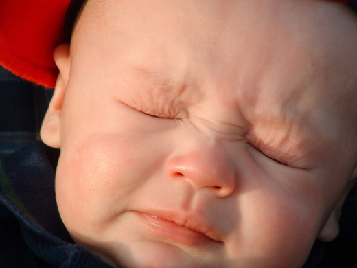 This baby is about to sneeze. Sneezing is one symptom of measles, although it's also a symptom of many other illnesses and of a minor nose irritation.