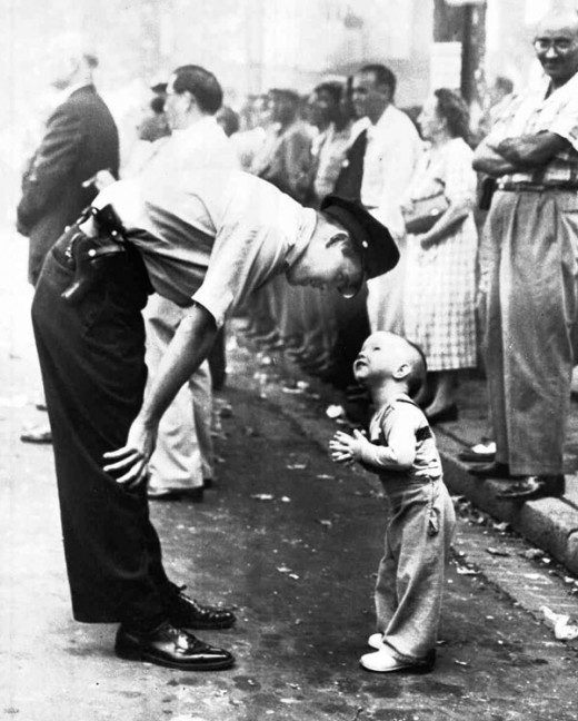 During a Chinese festival, officer Maurice Cullinane stooped down to ask Allen Weaver to move out of the way of the fireworks. The picture earned photographer Bill Beall a Pulitzer Prize.