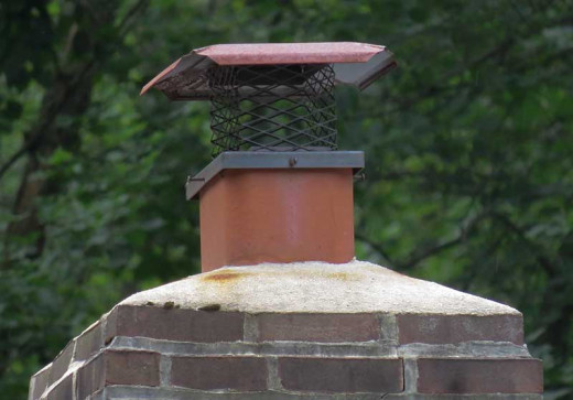 Concrete crown of masonry chimney encasing fireclay flue.