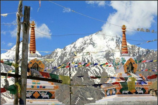 Stupas at Kunzum Pass with snow clad peaks in the background.
