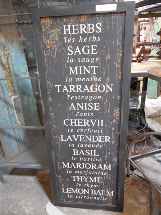 rustic black poster of various spices - herbs such as sage, mint, tarragon, etc..