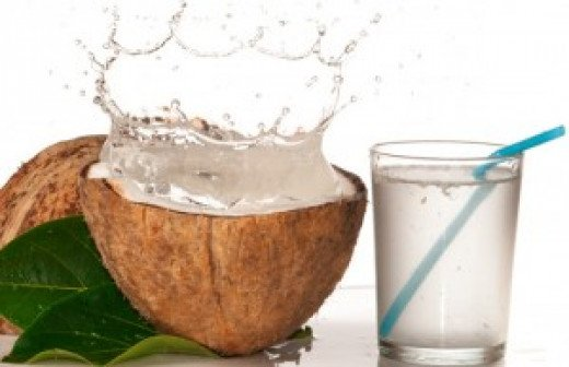A Coconut with coconut water splashing and a glass of coconut water.