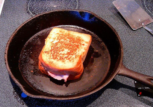 Grilled cheese sandwich in a cast iron skillet with ham