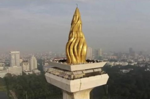 Monas, topped by a flame covered with gold foil.